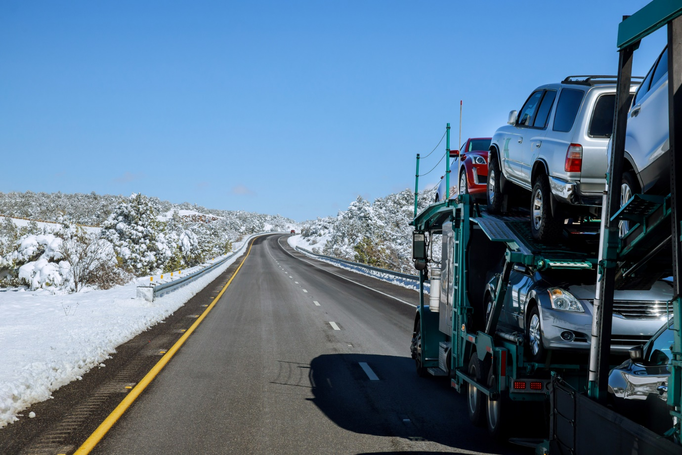 An auto carrier trailer driving on the road.