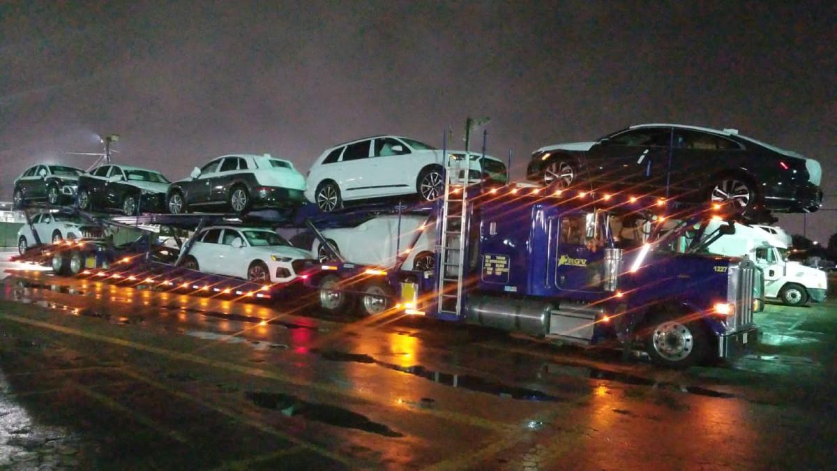 A truck full of vehicles being transported photographed en route.