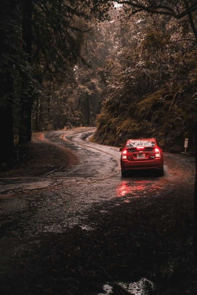 a red car driving through heavy rains.