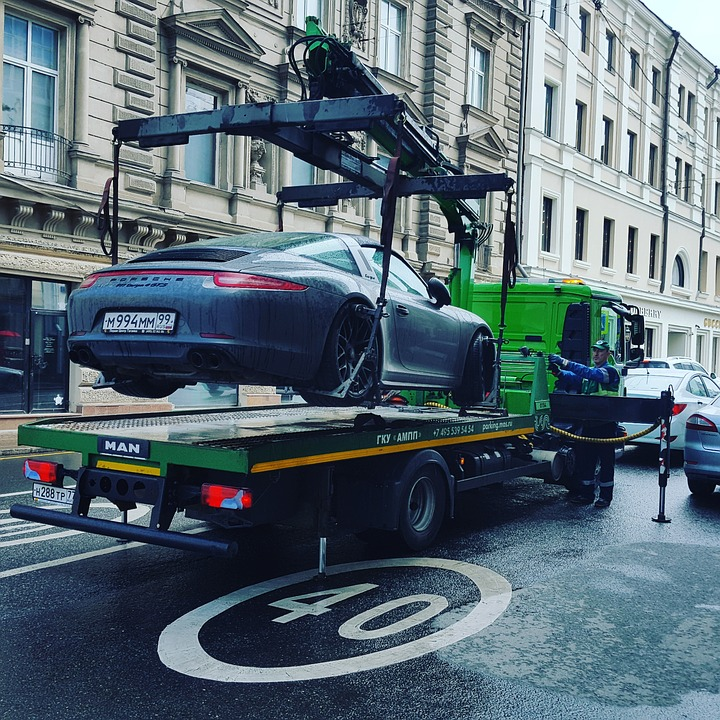 Car being towed and lifted onto a truck
